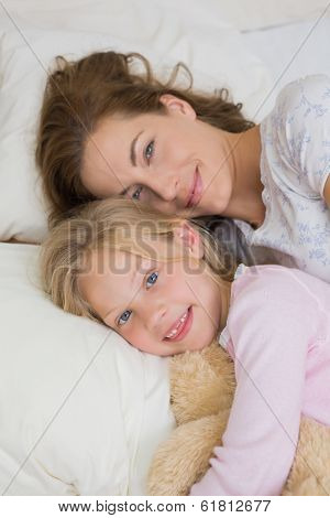 High angle portrait of a young girl and mother with stuffed toy resting in bed at home