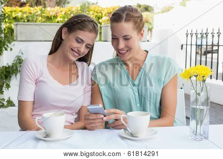 Two happy female friends reading text message at the coffee shop