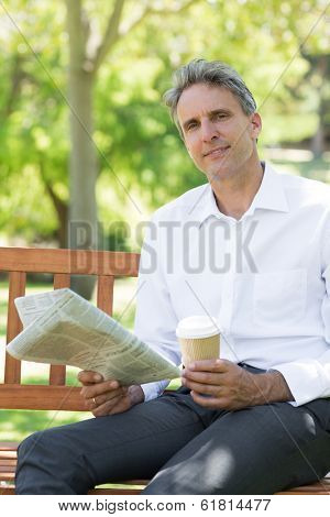 Portrait of businessman with disposable cup and newspaper in the park