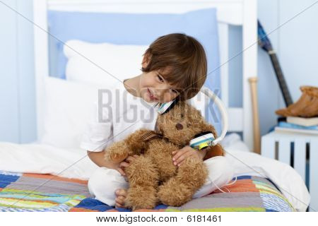 Little Boy Playing With Headphones And Teddy Bear