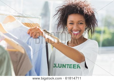Portrait of a smiling female volunteer by clothes rack