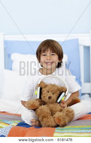 Happy Kid Playing With Headphones And Teddy Bear