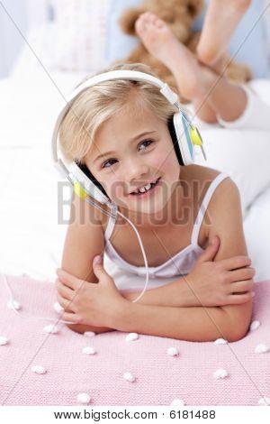 kleines Mädchen hören der Musik im Bett mit Kopfhörern