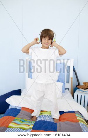 Little Boy With Headphones On Dancing In Bedroom