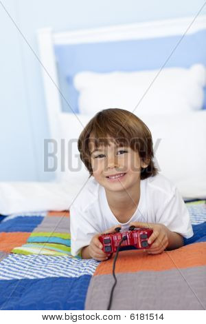 Smiling Boy Playing Videogames In His Bedroom