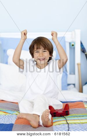 Happy Boy Playing Videogames In Bedroom