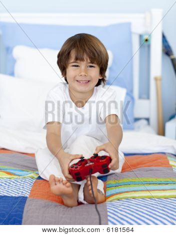 Boy Playing Videogames Sitting In His Bed