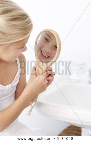 Little Girl Playing With A Mirror