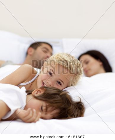 Little Girl Smiling Wile Her Family Sleep