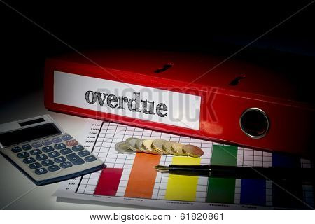 The word overdue on red business binder on a desk