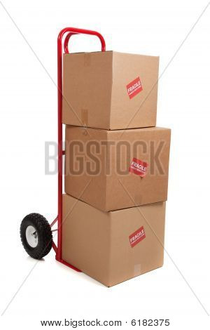 A Red Hand Truck On White With Boxes