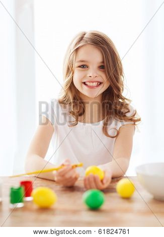 easter, holiday and child concept - smiling little girl coloring eggs for easter