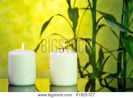 two white candles with bamboo on glowing yellow background