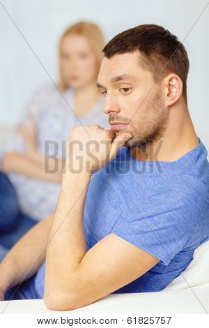 love, family and happiness concept - upset young man with man on the back at home