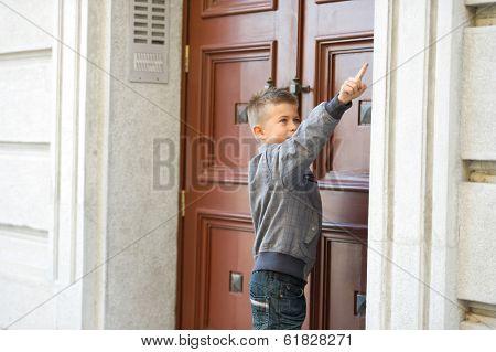 Little boy ringing doorbell