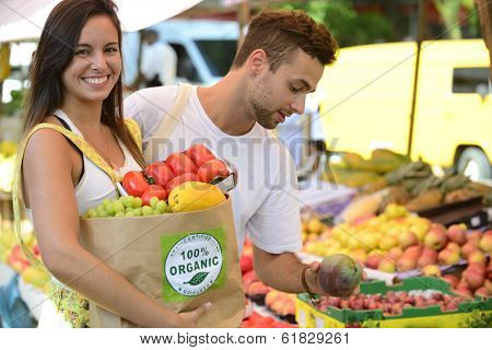 Happy couple shopping fruits and vegetables at a open street market, carrying a shopping paper bag with a 100% organic certified label full of fruit and vegetables.