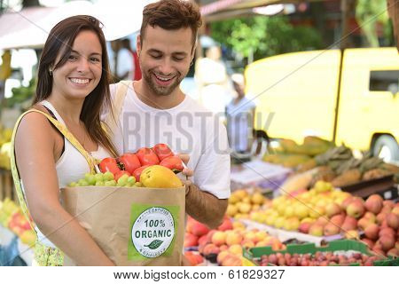 Couple shopping at open street market carrying a paper bag with a 100% organic certified label full of fruit and vegetables.