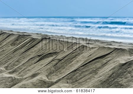 Steep Hill Of Sand Next To Ocean Waves