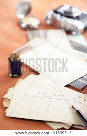 retro photo post cards , vintage ink , pen, blotter and camera on old leather table