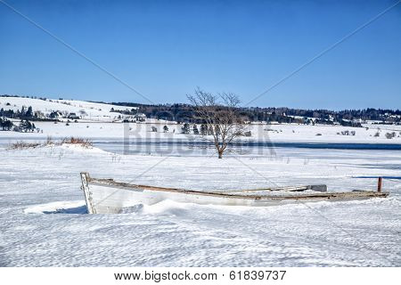 Old wooden rowboat buried in snow in rural Prince Edward Island.