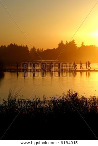 A group of people walking on the footpath on the lake at sunset