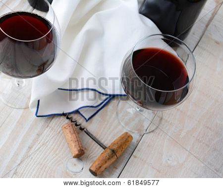Two wineglasses of red wine on a wood table with antique cork screw. Horizontal format shot from a high angle.