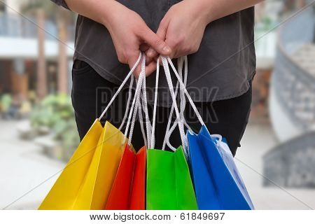 Woman Holding Colored Shopping Bags In A Mall In Her Hand