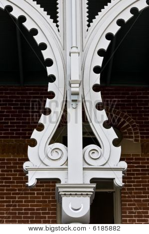 Ornate Column In  Front Of Brick Wall And Window