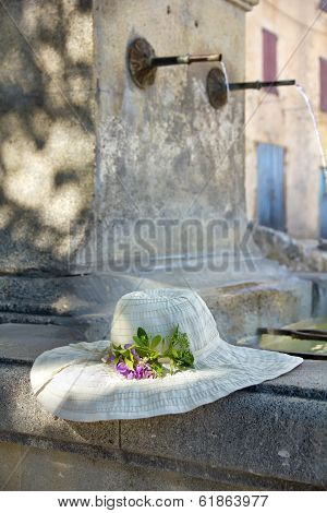 Sunhat With Real Flower On A Provencal Fountain In Porvence, France.