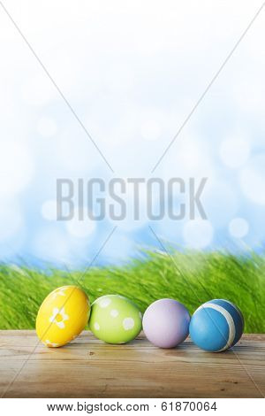Row of Easter eggs on wooden plank over fresh green grass background