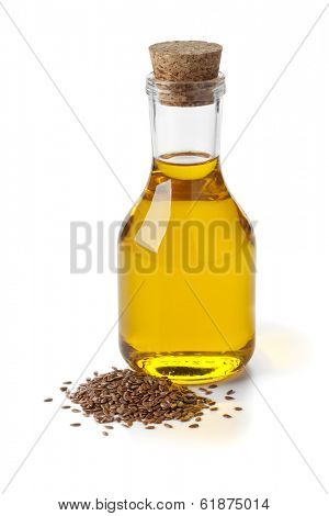 Bottle of flax seed oil ans seeds on white background