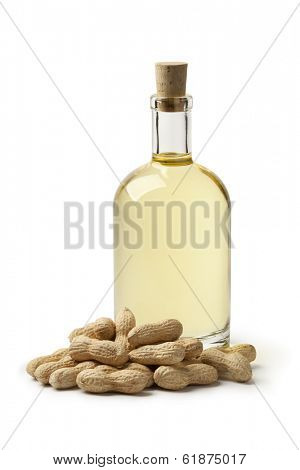 Bottle of peanut oil and peanuts on white background