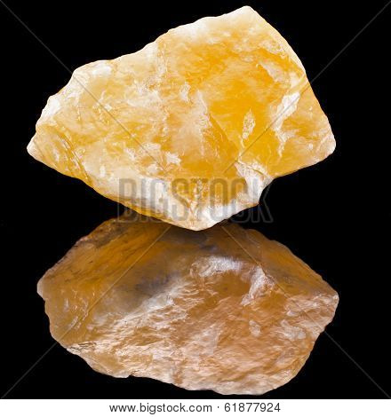 Calcite crystal mineral with reflection on black surface background