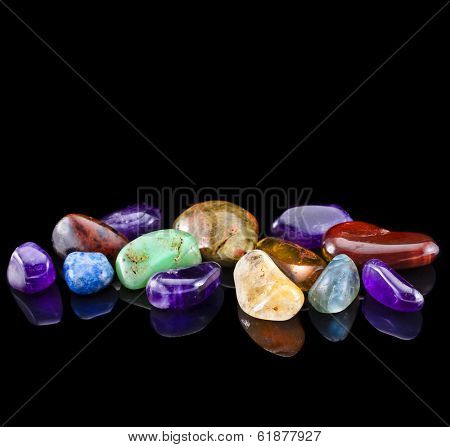 Semi-precious stones against black background with copy space for text