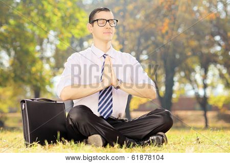 Businessperson with eyeglasses doing yoga exercise seated on a green grass in a park