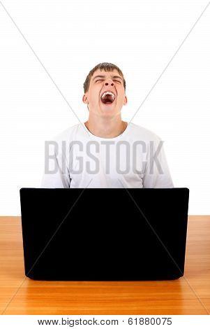 Teenager Yawning Behind Laptop