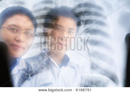 Two Asian Doctor Smiling Through The Xray Result