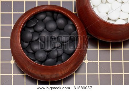 Black Go Stones In Wooden Bowl On Go Board