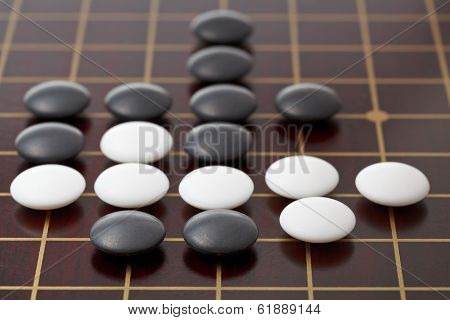 Go Game Playing By Stones On Wood Board
