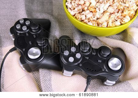 Black game controllers and bowl with pop corn on color plaid background