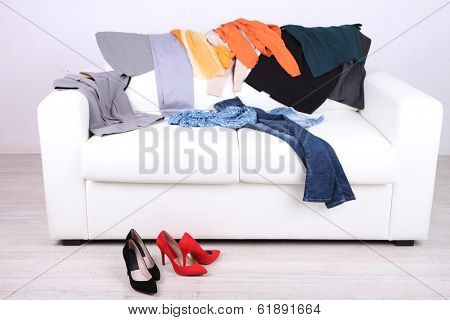 Messy colorful clothing on white sofa on white wall background