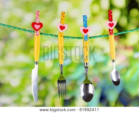 Cutlery dried on rope on natural background