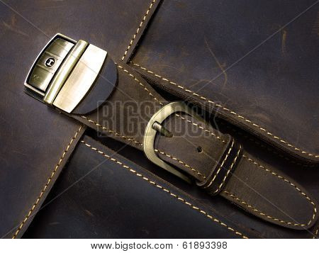 Brass metal clasp on old leather case with hand stitching