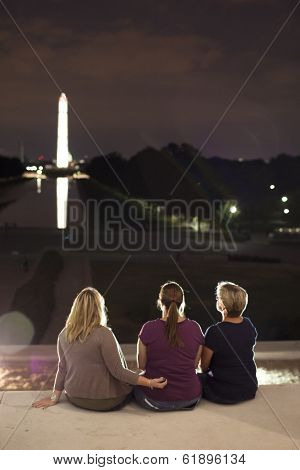 Three Women Sitting In Front Of Thomas Jefferson Memorial At Night