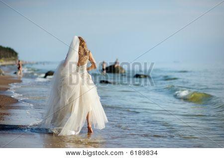 Novia caminando a lo largo de la costa del mar