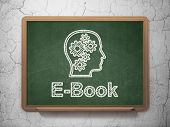 Education concept: Head With Gears and E-Book on chalkboard background