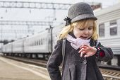 stock photo of bye  - Little girl standing on station waiting for a 