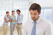 stock photo of half-dressed  - Colleagues gossiping with sad young businessman in foreground at a bright office - JPG