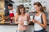 Portrait of female friends with male barista at counter in the coffee shop