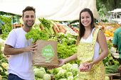 stock photo of papaya fruit  - Small business owner selling organic fruits and vegetables to a woman carrying a shopping paper bag with a 100 - JPG